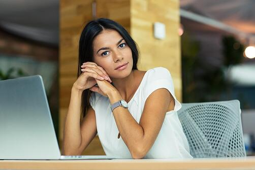 Portrait of attractive thoughtful businesswoman sitting at the desk in office and looking at camera.jpeg