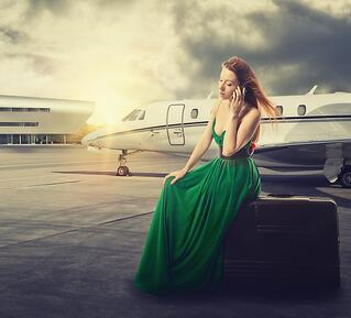 beautiful woman waiting for flight departure sitting on suitcase talking on mobile phone with airplane on background.jpg